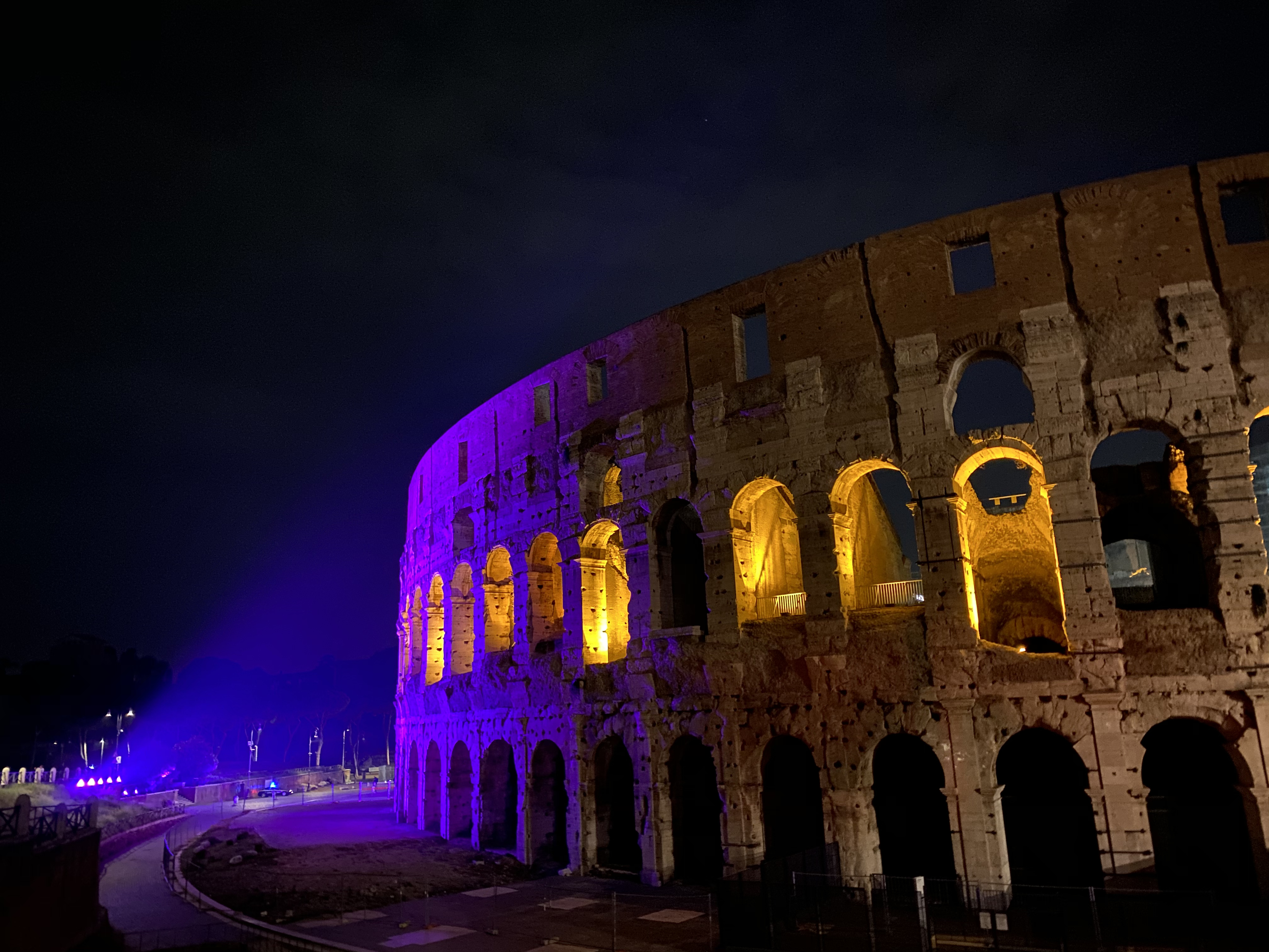 Purple lights hitting the Colosseum at night (wide lens).